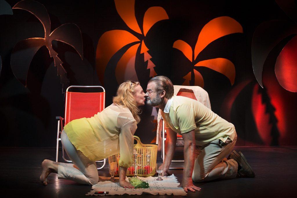 Camilla Blomqvistin lomaparatiisia koristavat digiajan äitelät värit. Onnellisuusmuurin takana osat ovat vaihtuneet. Komentoa pitää vaimo Anna-Karin (Sylvia Rauan) ja aviomies Erik (Benjamin Moliner) peesaa. Kuva Riksteatern