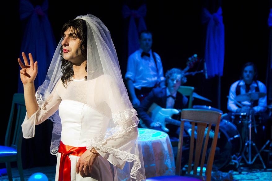 Sadettin Kirmiziyüz näyttellee sekä perheen tytärtä Sarea että hänen näyttelijäksi opiskelevaa pikkuveljeään. Kirmiziyüz on huikean hyvä stand up -koomikko ja ruutia esitykselle antaa taustalla näkyvä bändi, jonka jäsenet tekevät myös esityksen sivuroolit. Kuva Trouble Man/Tampereen teatterikesä