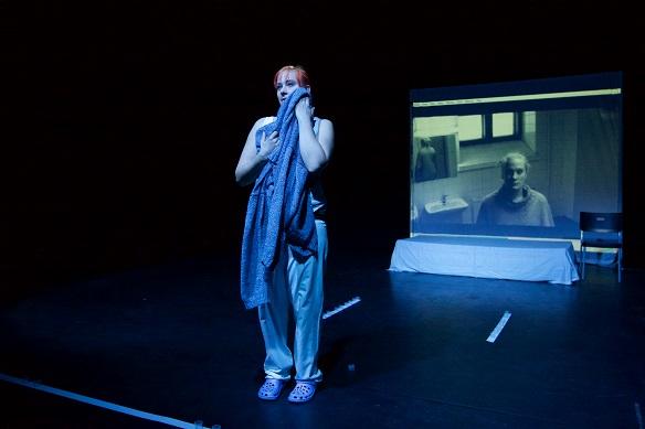 Kuva on otettu Johanna Haapäemäen esityksestä Työväen Näyttämöpäivillä Mikkelissa. Taustalla näkyy Catrine Krusbergin esitystä varten kuvaama video. Kuva Työväen Näyttämöpäivät/Jere Lauha